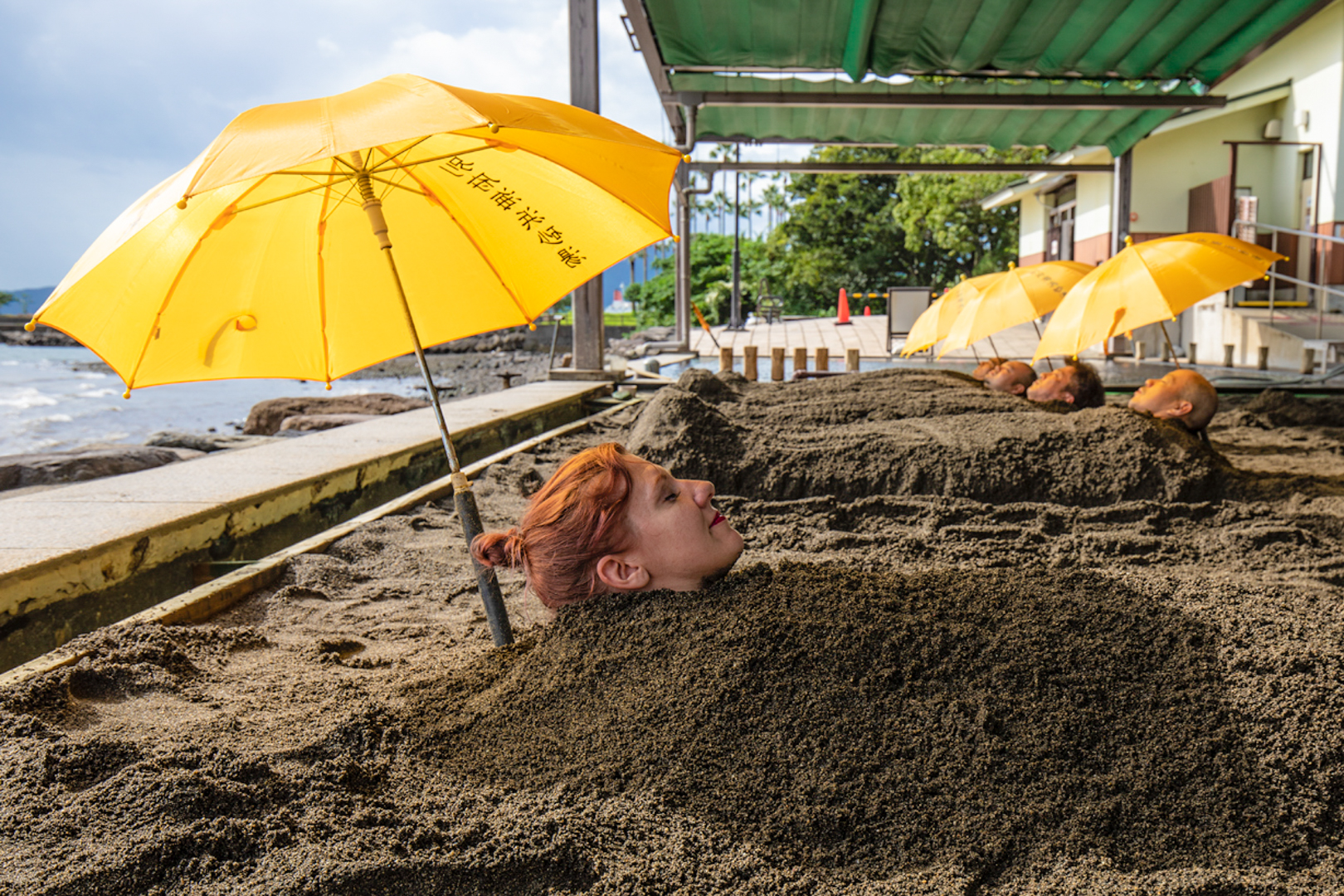 Visitors buried up to their necks in hot sand at the Beppu Beach Sandbox.