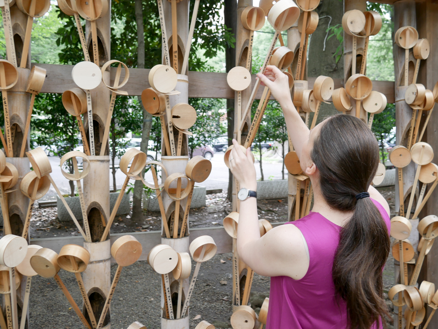 The author, Jessica, placing her bottomless ladle among the others as part of a safe birth prayer at a shrine in Tokyo.
