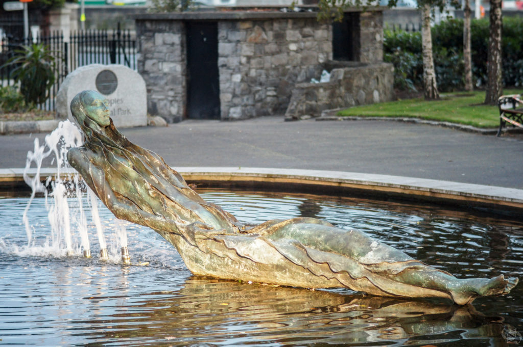 The Anna Livia Statue in Dublin. The statue is reclined in a small park fountain with long wavy hair and a ripply effect over her body, that looks much like a flowing dress.