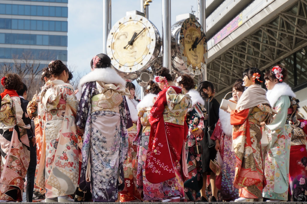 A group of Japanese women in formal furisode kimono stand underneath the clocks of Sun Plaza in Nakano Ward, Tokyo, ahead of their Coming of Age ceremony.