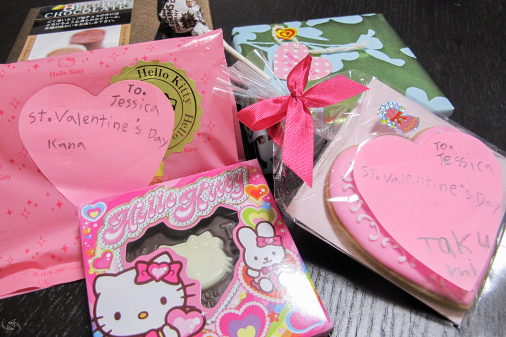 Several examples of giri choco for Japanese Valentine's Day laid out on a table, including a heart-shaped cookie in a bag with a pink bow, a Hello Kitty chocolate heart, small boxes of chocolates and a lollipop.