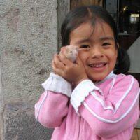 Girl in Peru holds guinea pig outside restaurant