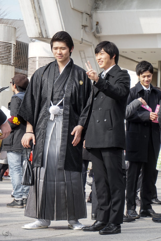 A man wearing traditional hakama poses for a photo next to a man wearing a Western style suit. The man in the suit is giving the peace sign.