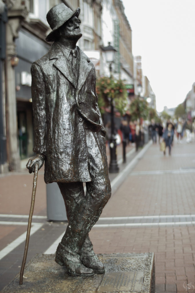 The James Joyce Statue in Dublin standing with one hand in his pocket and the other leaning on a walking stick.