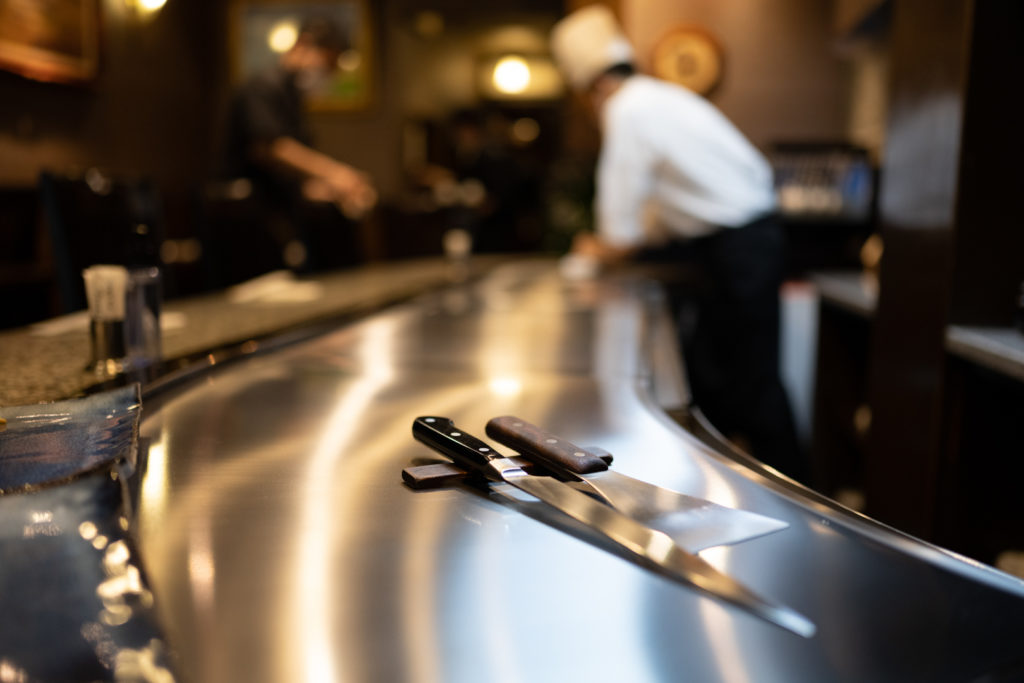 A knife and metal spatula sit on a hot plate prior to cooking kobe beef at a Japanese restaurant in Kobe.