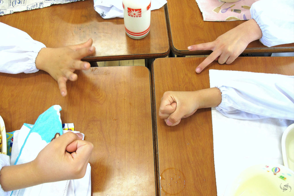 Four Japanese school students play janken at their desks over lunch. Two went for rock, one for paper and the other scissors.