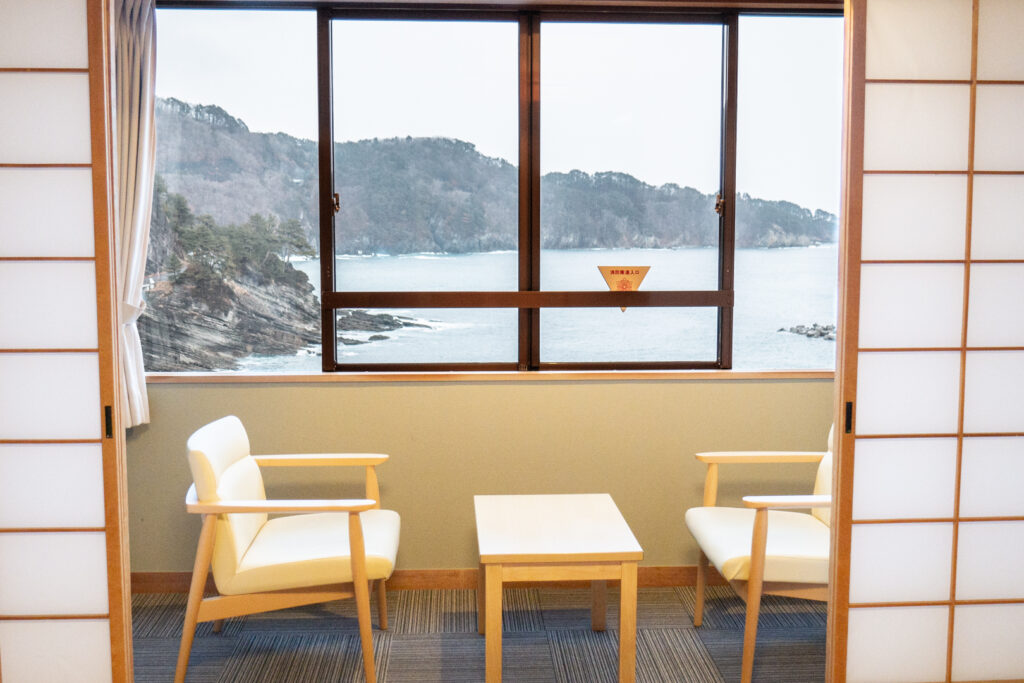 Japanese sliding screen doors open to a small sitting area with a table and two chairs and a coastal view out the window.