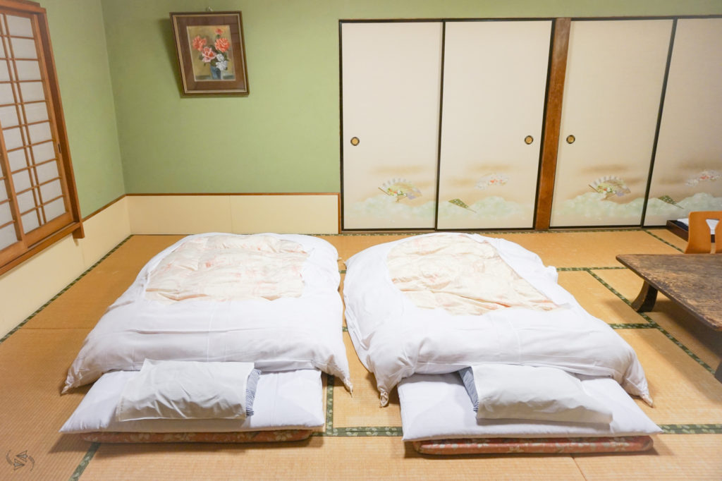 Two Japanese futons with white linen on traditional tatami mat flooring at an Airbnb in Japan.