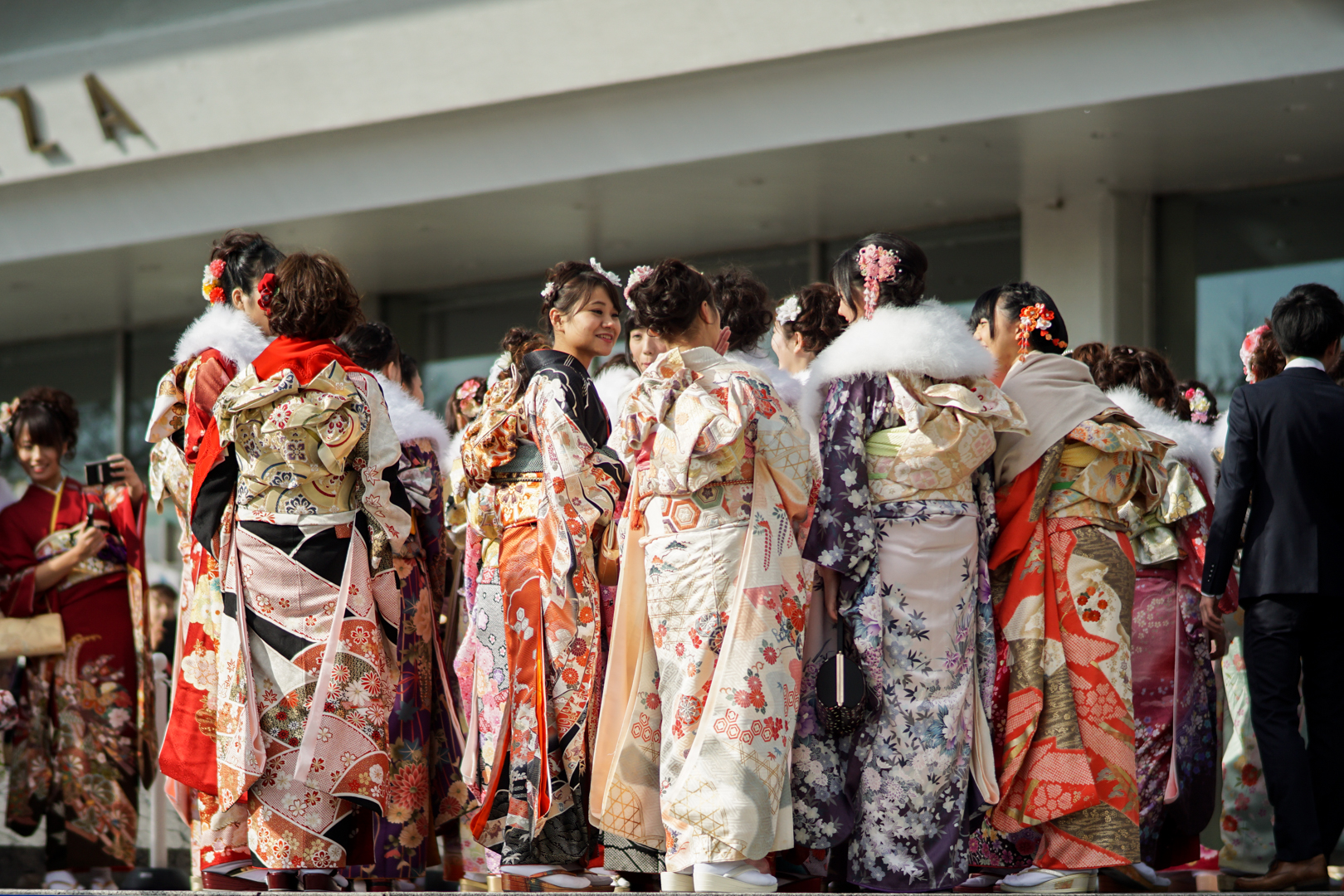 A group of Japanese women in formal furisode kimono stand chatting outside the venue of their Coming of Age Day ceremony in Tokyo.