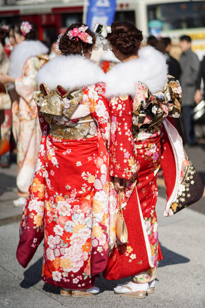 Two women with their backs to the camera, one holding up a smartphone to take a selfie, are all dressed up in their red kimonos with white fur stoles for Japan's Coming of Age Day.