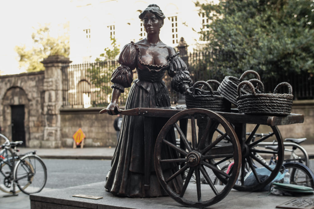 The Molly Malone statue in Dublin. Malone stands in a low-cut dress with puffy sleeves and long skirt, pushing a wooden trolley with three woven baskets sitting on top.