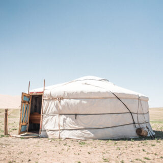 A photo by Patrick Schneider (via Unsplash). A single white ger stands on an arid swathe of land with the door open. The interior door is blue with an orange frame.