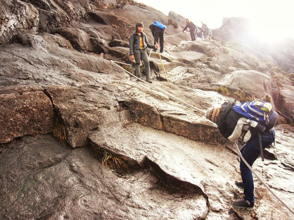 The author uses ropes to descend the steep rockface on the upper reaches of Mount Kinabalu, while the guide looks on.
