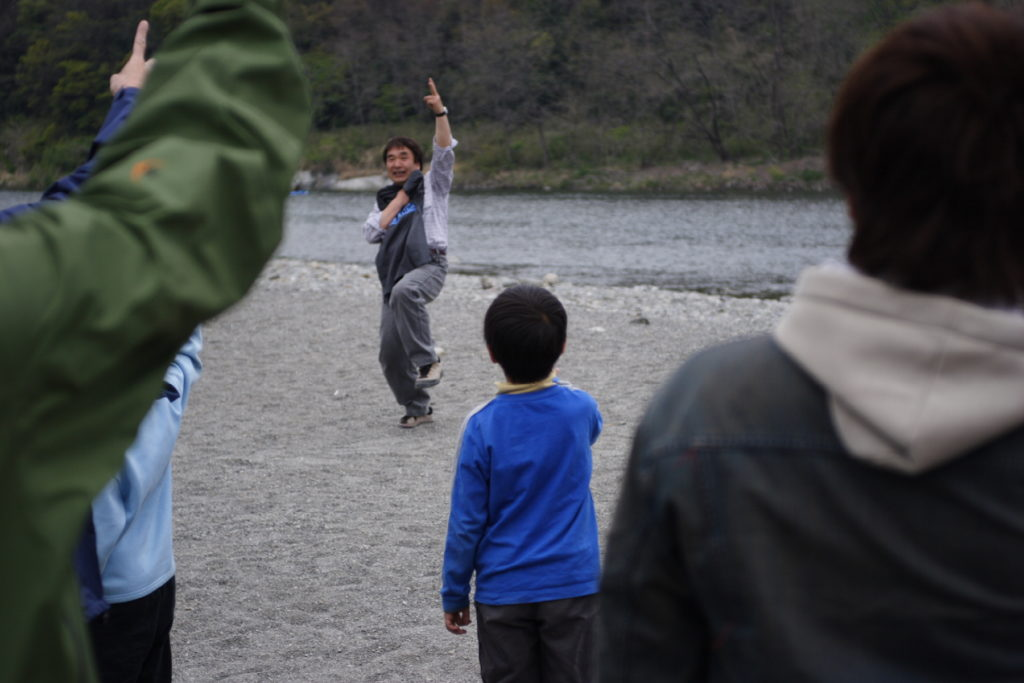 A group play multiplayer janken outdoors by a river. The central player can be seen energetically holding up scissors with his left hand. We can see the backs of four players in the group, holding up their chosen gestures.