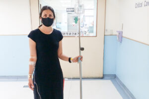 The author stands in a Taiwanese hospital wearing a black face mask with IV drip and stand, and multiple tapes and bandages from blood test attempts.