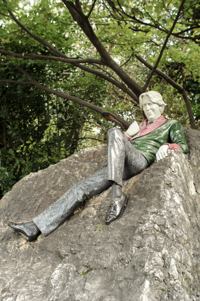The Oscar Wilde statue in Dublin. Wilde lays on a rock in a green jacket with red collar and cuffs, with one leg outstretched and the other knee bent. His facial expression looks quite smug with a half-smile that lifts one side of his face.