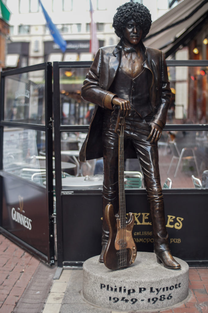 The Phil Lynott Statue in Dublin. Lynott stands wearing a buttoned up shirt and vest with a leather jacket and leather pants. One thumb rests casually in his pant pocket and the other is perched on the headstock of his guitar that is standing upright on the ground.