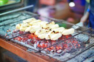 Bananas being grilled over coals.