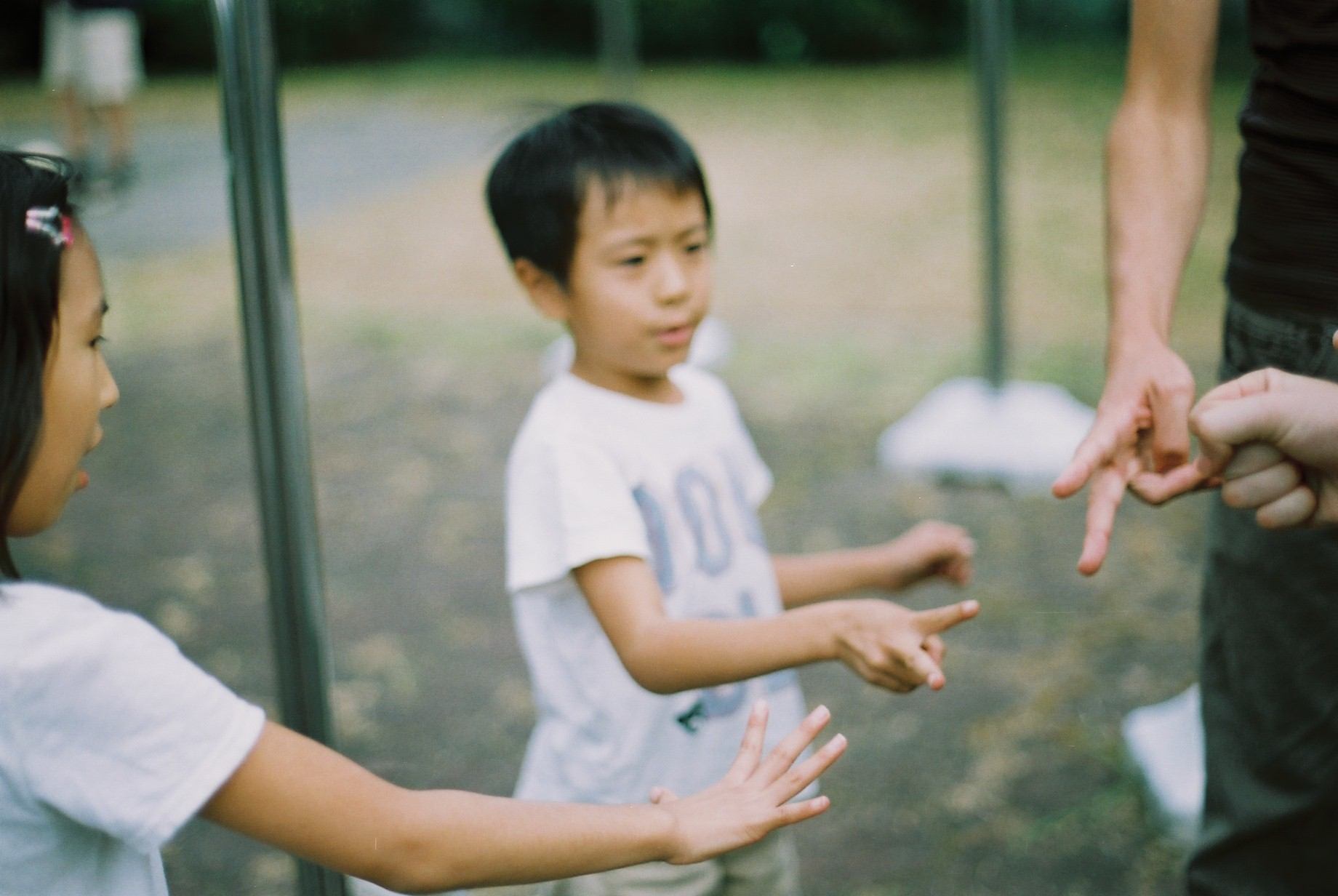 Four people, two children and two adults, play janken against one another outdoors. The girl chose paper, and the boy scissors, while the two adults (faces not shown) chose scissors and rock, resulting in a draw.
