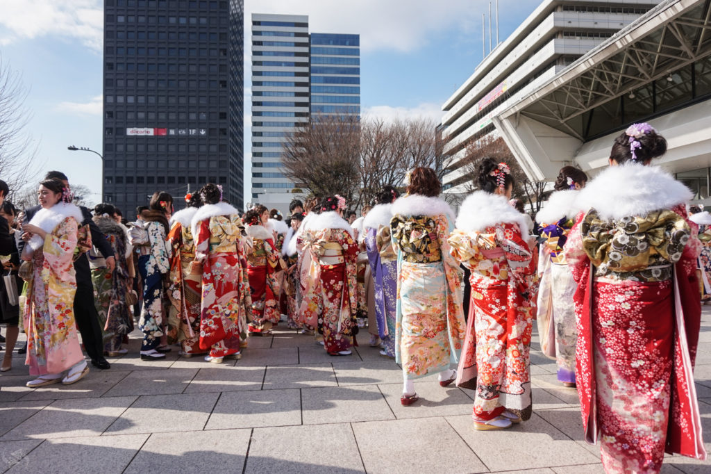 A group of Japanese women dressed in vibrantly colored furisode kimono gather in front of the venue of official Coming of Age celebrations in Nakano, Tokyo.