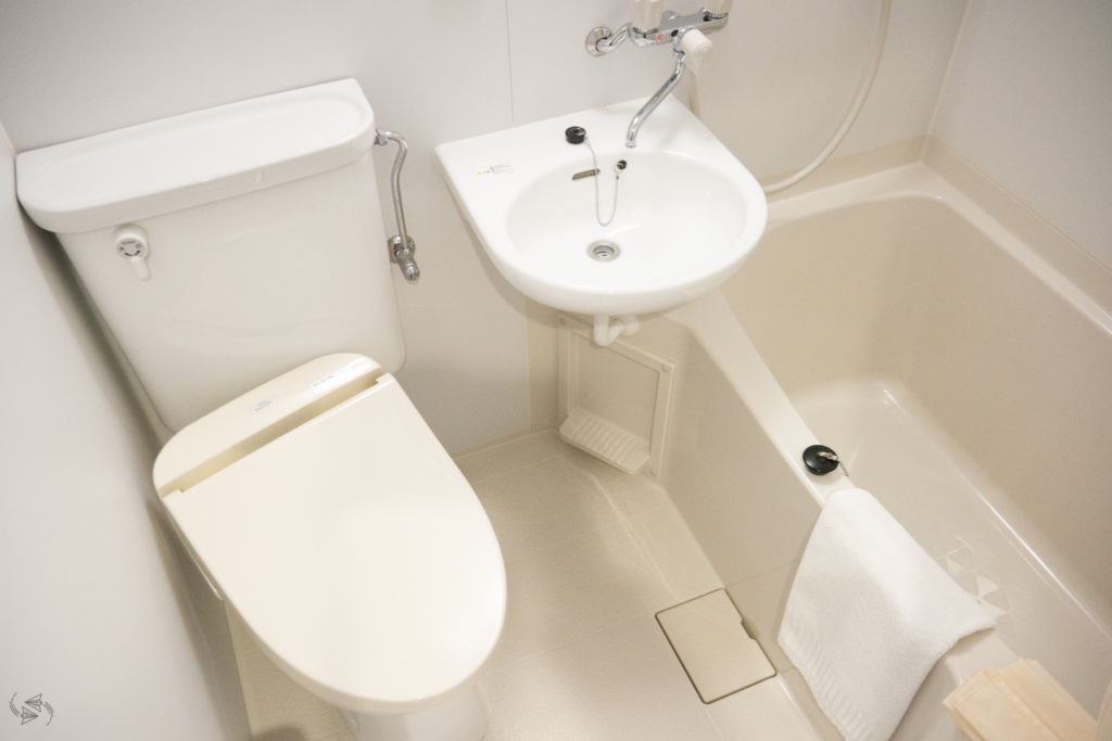 A small Japanese bathroom with the toilet, sink and bath tub all in the same room. The shower is over the bath.