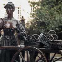 The Molly Statue, Dublin. Molly Malone stands in a low-cut dress with puffy sleeves and long skirt, pushing a wooden trolley with three woven baskets sitting on top.