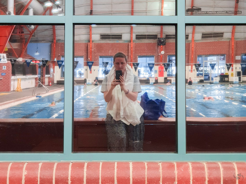 Author takes a post-swim photo of herself reflected in the windows at the indoor swimming pool. Behind her other patrons are doing laps in the pool.