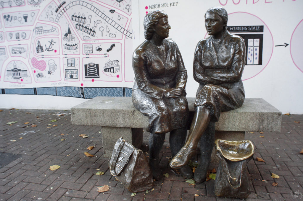 The Hags with the Bags Statue in Dublin. Two women sit on a bench close together and facing each other in conversation. The one on the left sits with her hands neatly on top of one another, and the one on the right has her legs crossed and arms folded. They both have bags at their feet, the one on the left closed and the one on the right open.