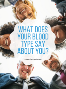 A group of women and men of different ethnicities are huddled in a circle looking down at the camera in the middle. A white-colored icon in the center with blue text reads, 'What does your blood type say about you?' In black text below it, 'notesofnomads.com'.