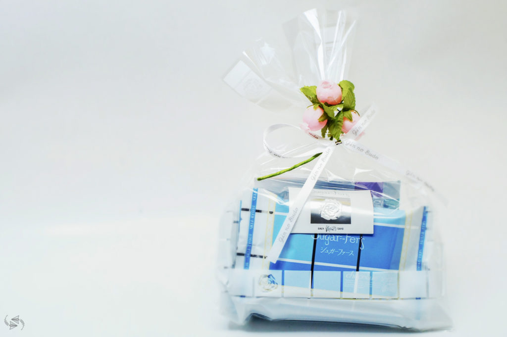 A White Day gift. Blue and white-packaged sweets inside a clear bag with a white ribbon and artificial pink flowers with green foliage to tie the bag up.