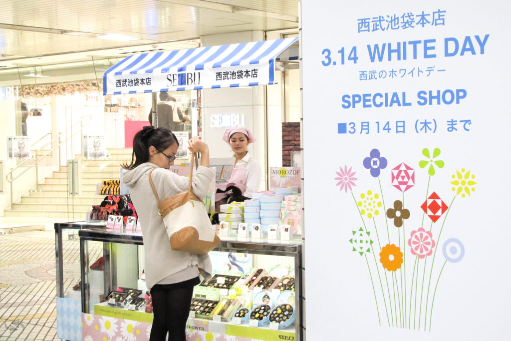 A woman reaches into her purse to get her wallet at a special Seibu department store pop-up White Day shop selling an array of boxed chocolates for the occasion. A big sign to the right of the store says '3.14 White Day Special Shop, until March 14th' with an image of a bunch of flowers underneath.