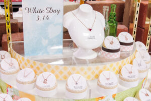 A tiered jewelry display in a department store, showcasing various necklaces, next to a sign that says 'White Day 3.14'.