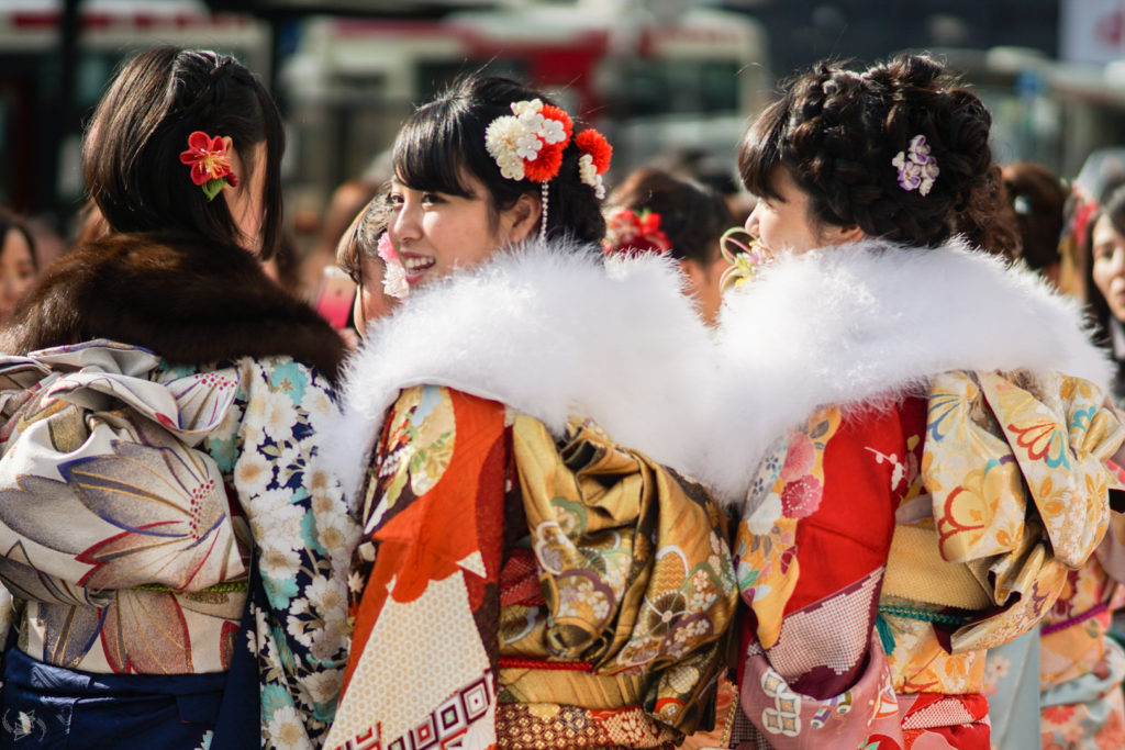 Three Japanese women wearing formal furisode kimono for Seijin no Hi stand together, two facing away, while the one in the middle looks back towards the camera. The one in the middle and the one on the right wear white fur stoles over their striking red, orange and gold kimonos.